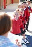Lärare Taking School Register i lekplats arkivfoto