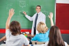 Lärare Teaching While Students som lyfter händer Arkivfoto