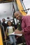 Lärare Unloading Elementary Students från skolbussen royaltyfri bild