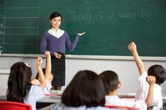 Lärare vid den Blackboard I kinesskolan Arkivfoto