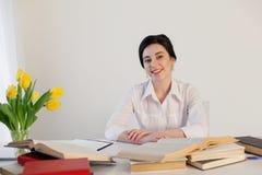 Lärareaffärsdamen läser böcker i kontoret arkivfoton