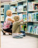 LärareAnd Boy Selecting böcker i arkiv Arkivbilder