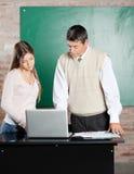 LärareAnd Student Using bärbar dator på skrivbordet in Royaltyfri Bild