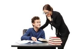 Lärareanseende bredvid studentens skrivbord och studenten poi Royaltyfri Bild