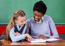 LärareAssisting Schoolgirl At skrivbord arkivfoton