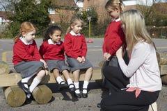 LärareComforting Victim Of pennalism i lekplats royaltyfria bilder