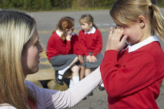 LärareComforting Victim Of pennalism i lekplats Arkivbild