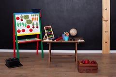 Läraredagbegrepp och baksida till skola Sikt av inre av grundskolan tom lokalskola Jordklot, blyertspennor och ställning fo royaltyfri foto