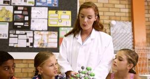 Lärareförklaring ungar om molekylär modell i laboratorium stock video