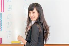 Lärarehandstil på whiteboarden som tillbaka ser på cla Fotografering för Bildbyråer