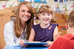 LärareHelping Elementary Scool elev som använder den Digital minnestavlan arkivfoto