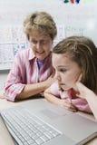 LärareHelping Schoolgirl Use bärbar dator royaltyfri foto