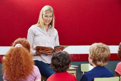 Lärareläsning från boken i grupp arkivfoto