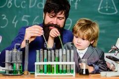 Lärareman med pysen fader och son på skola Liten unge som lär kemi i skolalaboratorium Dra tillbaka till royaltyfria bilder