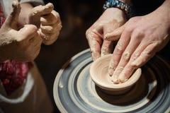 Läraremannen undervisar ett barn hur man gör en keramisk platta på keramiker`en s att trava Arkivbilder
