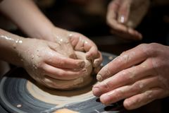 Läraremannen undervisar ett barn hur man gör en keramisk platta på keramiker`en s att trava Arkivfoton