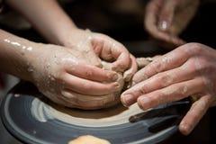 Läraremannen undervisar ett barn hur man gör en keramisk platta på keramikerna att trava Royaltyfri Foto