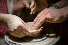 Läraremannen undervisar ett barn hur man gör en keramisk platta på keramikerna att trava Arkivbild