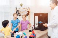 Läraren berättar barnen under kursen hur skrivaren 3D fungerar Royaltyfria Bilder