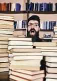Läraren eller studenten med skägget bär glasögon, sitter på tabellen med böcker som är defocused Nerdbegrepp Man nerd på royaltyfri fotografi