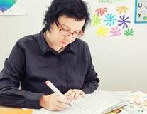 Läraren för det engelska språket kontrollerar studentanteckningsboksammanträde på arkivbilder