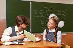 Läraren förklarar den svåra uppgiften för studenten Royaltyfria Bilder