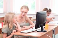 Läraren förklarar uppgiftsskolflickan Arkivbild