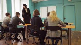 Läraren går förbi skrivbord och kontrollframsteg av studenter under en kurs lager videofilmer