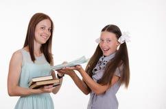 Läraren ger studenten anteckningsböcker Royaltyfria Bilder