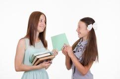 Läraren ger studenten en bevisad anteckningsbok Arkivbild