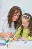 Läraren hjälper lilla flickan Arkivfoto