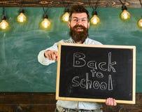 Läraren i glasögon rymmer svart tavla med inskriften tillbaka till skolan tillbaka begreppsskola till Man med skägget och Royaltyfri Foto