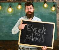 Läraren i glasögon rymmer svart tavla med inskriften tillbaka till skolan tillbaka begreppsskola till Man med skägget och Arkivbild