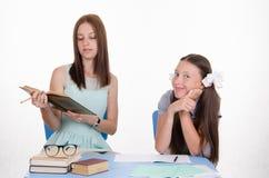 Läraren läser studentuppgifter från läroboken Royaltyfri Fotografi