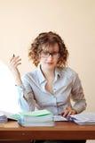 Läraren med en penna i hand sitter på ett skrivbord i klassrumet och chen royaltyfria bilder