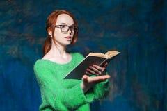 Läraren med rött hår i exponeringsglasläsebok och gestikulerar Arkivbild