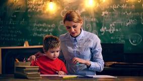 Läraren och pojken är förlovade i ett studentrum lära för begrepp Lärare och deltagare tillbaka skola till stock video