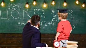 Läraren och skolpojken vände tillbaka framme av det gröna brädet Unge i avläggande av examenlock som lär former Vuxen människa so royaltyfri bild