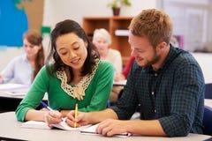 Läraren och studenten arbetar tillsammans på vuxenutbildninggrupp Arkivfoto