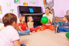 Läraren och ungar sitter i cirkellek med bollen royaltyfria foton