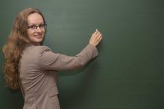 Läraren skriver på brädet Fotografering för Bildbyråer