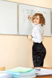 Läraren står på svart tavla och handstilen i klassrumet Arkivfoton