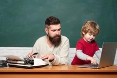 Läraren undervisar en student att använda ett mikroskop Lycklig familj - pappa och son tillsammans Mannen undervisar barnet homes arkivbild