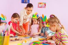 Läraren undervisar förskole- ungar i konstgrupp Arkivfoto