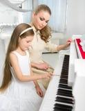 Läraren undervisar lilla flickan att spela pianot arkivbild