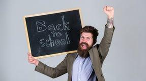 Läraren uppsökte mannen står och rymmer svart tavlainskriften tillbaka till skolagrå färgbakgrund Läraren annonserar tillbaka til arkivbilder