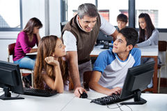 LärareUsing Computer With studenter i klassrum Arkivbilder