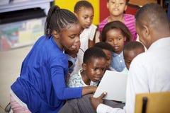 Lärarevisningen lurar en bok under grundskolakurs fotografering för bildbyråer