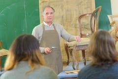 Lärarevisningstudenter hur man reparerar stol Royaltyfria Foton