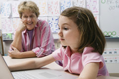 LärareWatching Schoolgirl Use bärbar dator Royaltyfria Bilder